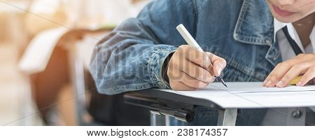 Exam With School Student Having A Educational Test, Thinking Hard, Writing Answer In Classroom For