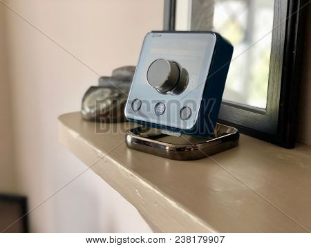 DUNWICH, SUFFOLK - APRIL 25, 2018: A Hive Smart Thermostat on a stand inside a house in Dunwich, Suffolk, UK. The technology allows central heating to be controlled from a smartphone.