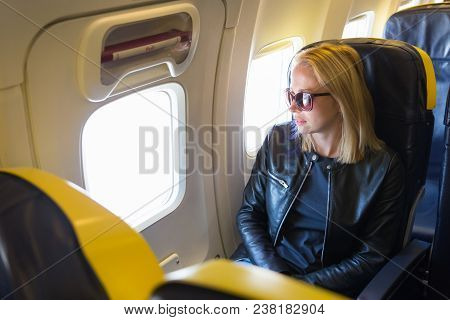 Woman Looking Through The Window On Airplane During Flight. Female Traveler Seated In Passanger Cabi