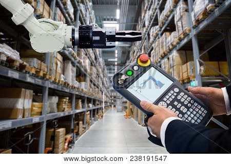 Engineer With Teach Pendant Device. Programming Robot With Robotic Arm In Warehouse
