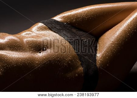Sexy And Erotic Body Parts Close-up Of A Beautiful, Slim And Muscular Woman In Black Lingerie. Water