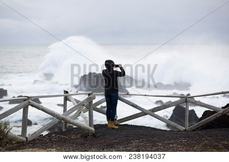 Wild, Stormy Weather, Weavy Ocean, Rocky Shore, Wooden Fence, Woman In Black Look At The Sea.