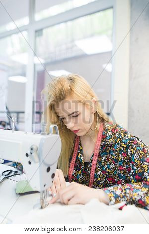 A Young Seamstress Is Working On A Sewing Machine In The Workplace. Beautiful Girl Works On A Sewing