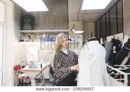 Young Fashion Designer Standing In The Studio And Trying On Clothes On A Mannequin. Creation Of Fash