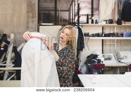 Young Dressmaker Woman Standing At The Dummy In The Studio And Measures The Clothes. Creation Of Fas
