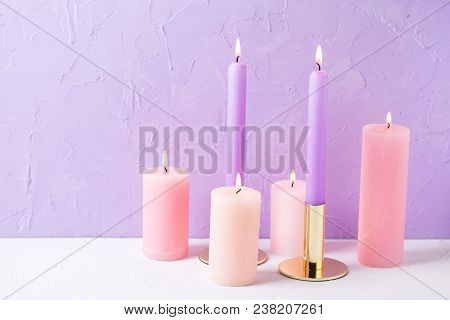 Pink Color Burning Candles Near By Violet Textured Background. Place For Text. Selective Focus.