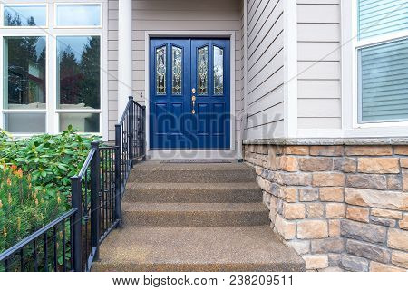 House Front Entrance With Concrete Steps Iron Rod Railing And Navy Blue Double Doors