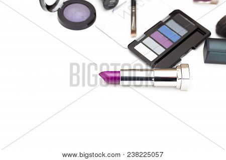 Purple Lipstick And Other Cosmetics On A White Background. Copy Space