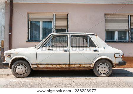 Old White Rusty Fiat Zastava 101 Car Made In Kragujevac City, Abandoned On The Street. April - 23. 2