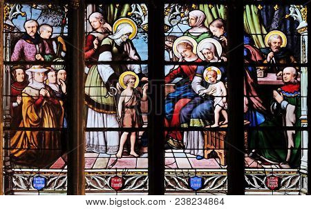 PARIS, FRANCE - JANUARY 04, 2018: St. John the Baptist introduced by his mother, St. Elizabeth, the Infant Jesus and the Holy Kinship, stained glass window in Saint Severin church in Paris, France.