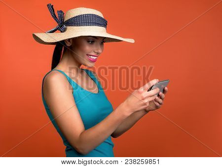 Pretty Girl With Hat On Head Looking At Cellphone In Her Hands With Joy. Isolated On Background