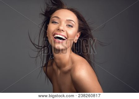 Portrait Of Good Looking Undressed Girl Laughing At Camera. Her Hair Is Streaming. Isolated On Backg