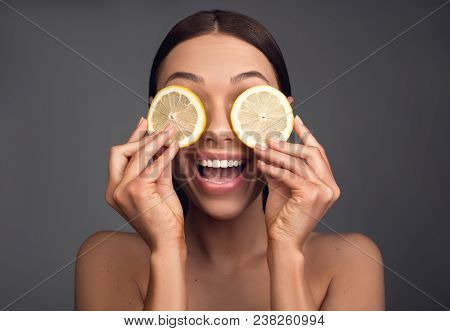 Vitality Concept. Portrait Of Enjoyed Appealing Woman Covering Eyes With Citrus Slices. Isolated On