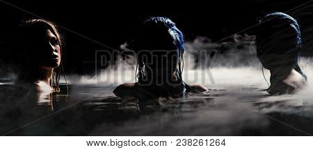 Sirens Of The Night. Two Mysterious Sirens In Fog Covered Water. Night Scene With Female Models. Bri