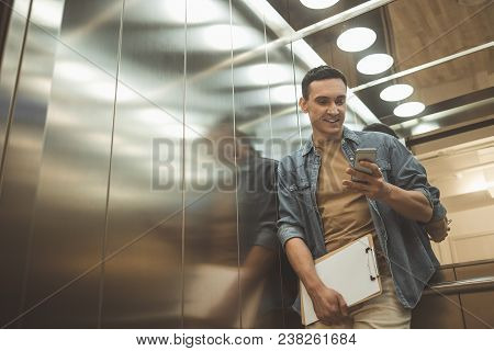 Low Angle Portrait Of Cheerful Employee Using Mobile While Standing In Lift. He Holding Documents N
