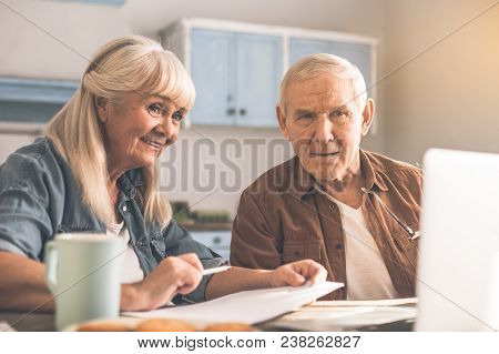Waist Up Portrait Of Excited Mature Married Couple Looking At Laptop With Interest And Smiling. They