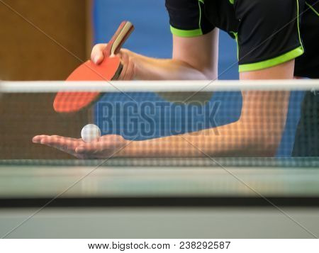 Table Tennis Player serving, focus at the ball in the background behind the net