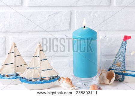 Coastal Living Background. Blue Burning Candle,  Decorative Boats And Sea Star  Near By White Brick