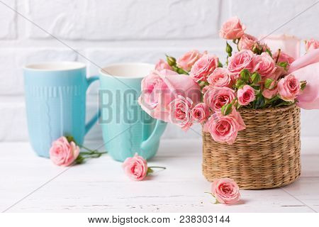 Pink Roses Flowers And Colorful Blue Cups Against  White Brick Wall. Floral Still Life.  Selective F