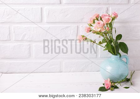 Tender Pink Roses Flowers In Blue Vase  On  White Wooden Background Near By Brick Wall. Floral Still
