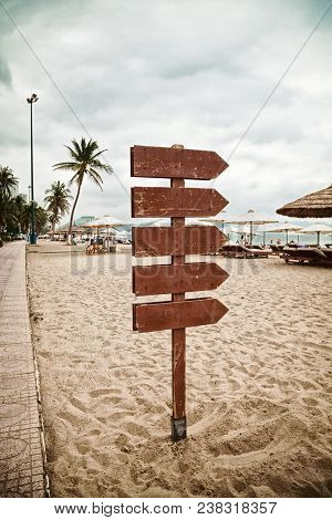 Wooden Pointer Post With Copy Space At The Beach. Blank Arrows On A Guidepost Pointing At The Sea. S