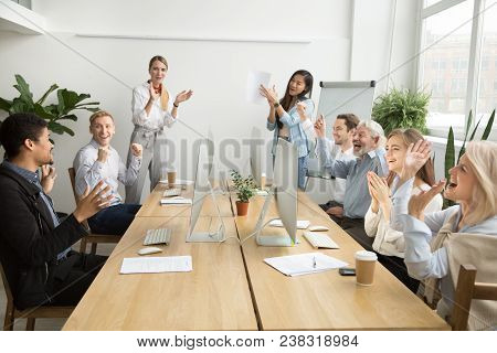 Corporate Diverse Team Colleagues Congratulating Motivated African Coworker With Business Success Or