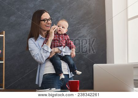 Happy Beautiful Business Mom Working In Office While Spending Time With Her Cute Baby. Business, Mot