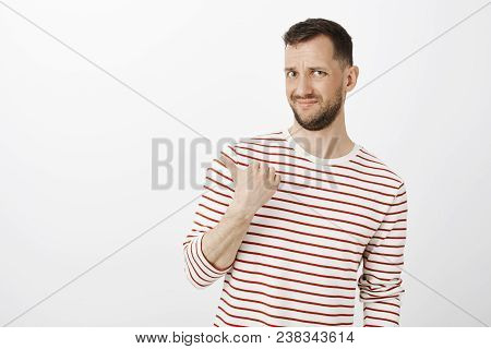 Who Invited That Guy. Portrait Of Displeased Doubtful Attractive Male In Striped Pullover, Grimacing