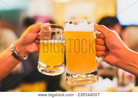 Friends Or Coworkers Cheering With Beer, Celebrating Together At Restaurant Or Night Club. Young Peo