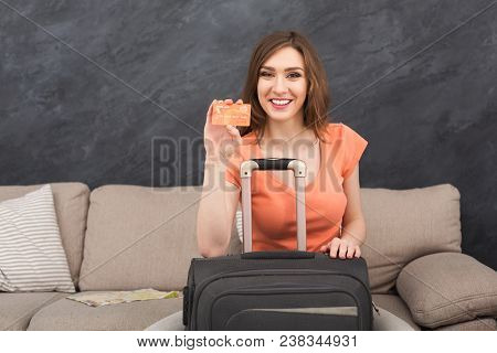 Young Cheerful Woman Showing Credit Card On Camera, Sitting With Packed Suitcase, Ready For Annual V