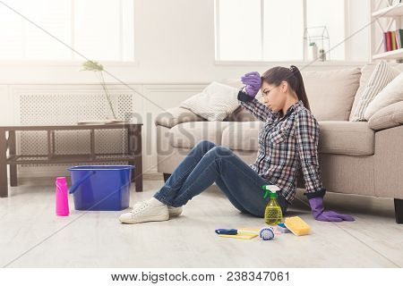 Tired Woman Cleaning Floor With Lots Of Tools. Young Tired Girl Surprised Of Detergents Quantity, Co