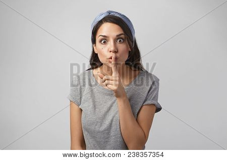 Conspiracy And Secrecy Concept. Isolated Shot Of Attractive Emotional Young Woman With Many Secrets