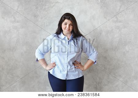 Portrait Of Attractive Friendly Looking Young Big-boned Overweight Brunette Woman Model Wearing Blue