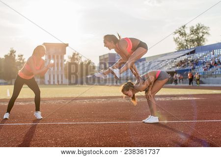 Fit Women In The Stadium Playing Leap Frog