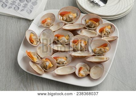 Dish with open cooked smooth clams as a gourmet