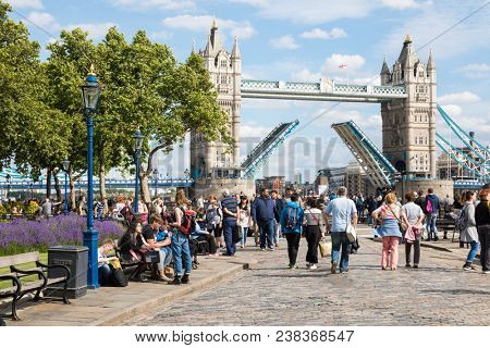 London, UK - 7th June 2017: People stroll along the banks of the River Thames on a summer day. The iconic Tower Bridge is opening for a passing vessel.