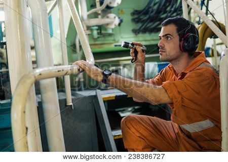 Marine Engineer Inspecting Ship's Engine In Engine Control Room