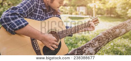 Female Fingers Playing Guitar Outdoor In Summer Park. Musician Woman And Her Guitar In Nature Park,