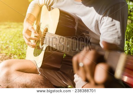Man Fingers Playing Guitar Outdoor In Summer Park. Musician Man And Her Guitar In Nature Park, Pract