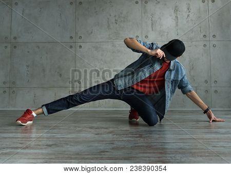 Teenager Guy In Denim Jacket And Baseball Cap, Jeans And Red Sweater Dances Of Break Dance. Dynamics