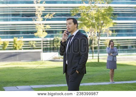 Serious Purposeful Handsome Young Male Manager Talking On Phone And Contemplating City Park. Ambitio
