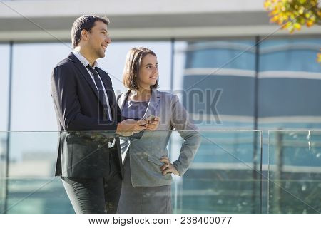 Smiling Pensive Business Colleagues In Formalwear Looking Into Distance And Contemplating Cityscape.