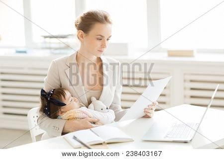 Busy young office manager with sleeping bbay daughter on hands sitting by desk and reading new contracts to sign