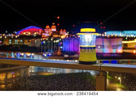 Luminous Hand Lantern Standing On The Fence Of Balcony On The Background Of Illuminated Buildings Of