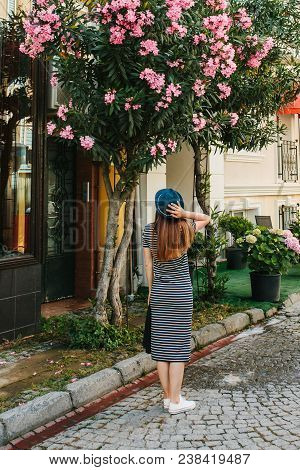 A Young Girl In A Hat Admires The Beautiful Flowers Next To The House
