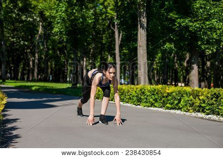 Young Sportive Girl In A Bright Blue Sport Bra And Black Leggings Starting Running In The Park. Phot