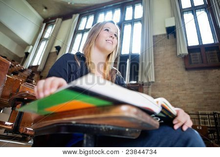Low angle view of young college girl paying attention in lecture