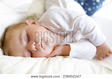 Cute Adorable Baby Girl Of 6 Months Sleeping Peaceful In Bed At Home. Closeup Of Beautiful Peaceful