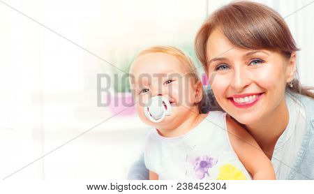 Mother and Baby kissing and hugging at Home. Happy Smiling Family Portrait. Mother and her Baby together. Love. Happy Mother and Baby with dummy kissing and hugging. Beautiful Family