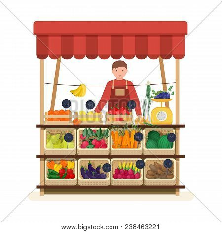 Man Standing At Counter Of Greengrocer's Shop Or Marketplace And Selling Fruits And Vegetables. Male